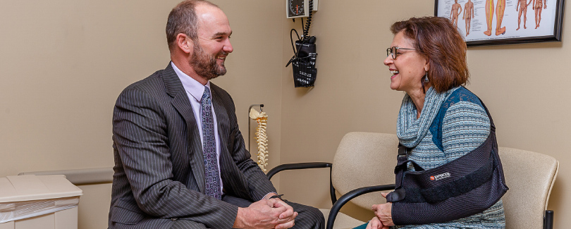 Male Dr speaking with female patient at Vermillion Medical Center about Orthopedic care