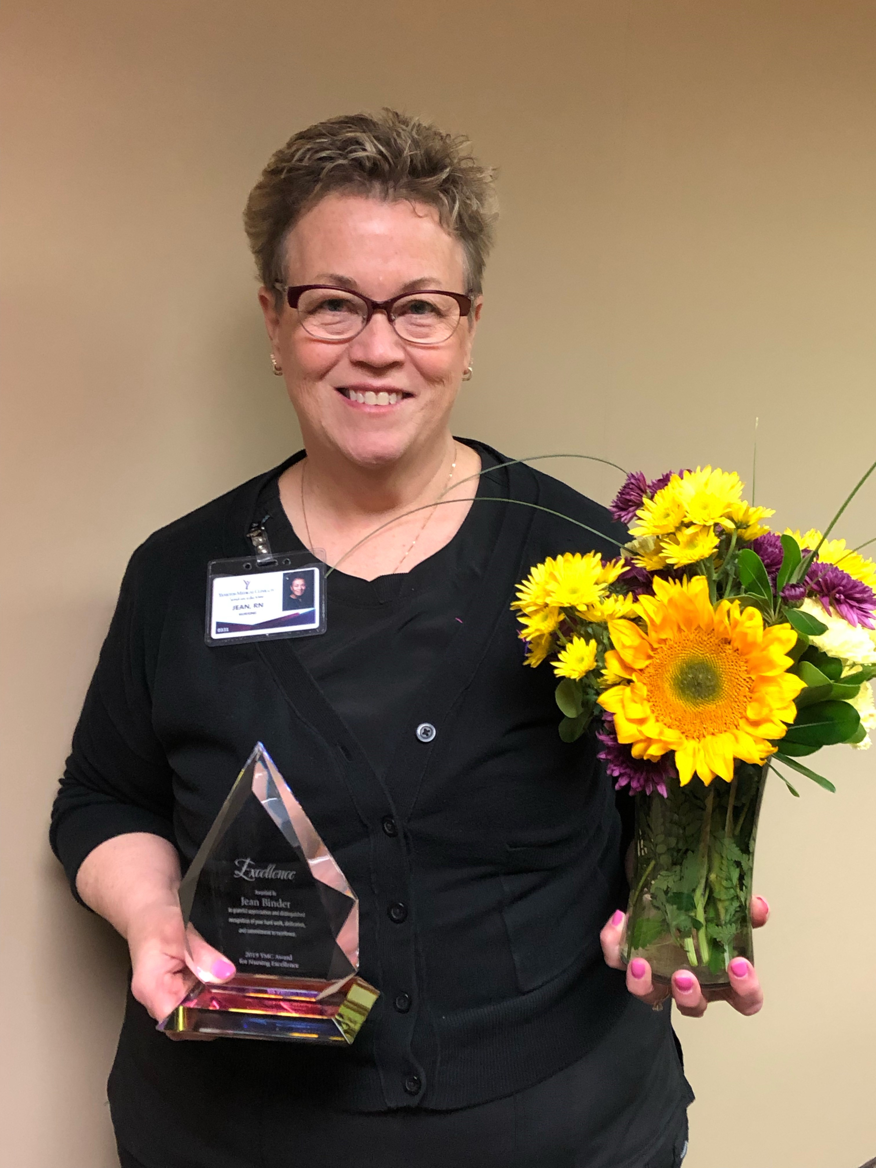 Jean Binder, RN, holds the excellence in nursing award and bouquet of flowers