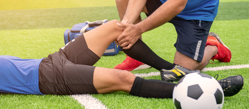 Soccer Player Laying On Field With Injured Knee